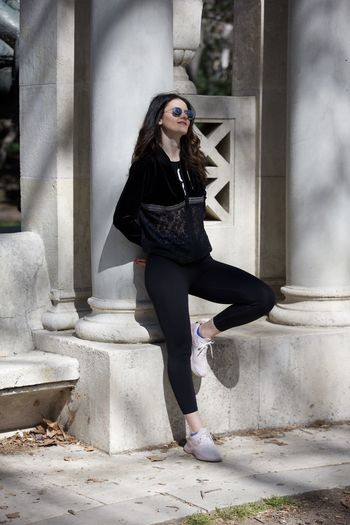 Fashionable mid adult woman wearing black clothing and sunglasses in city