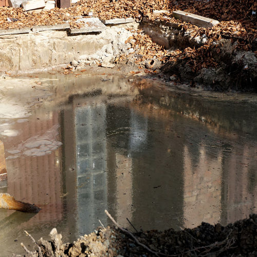 Reflection in an excavation pit with groundwater on which a thick, greasy layer of heating oil floats Reflection Remediation Architecture Building Building Exterior Built Structure City Day Destruction Diesel Dirt Environment Groundwater History Nature No People Oil Old Outdoors Pollution Puddle Reflection Transparent Water Window