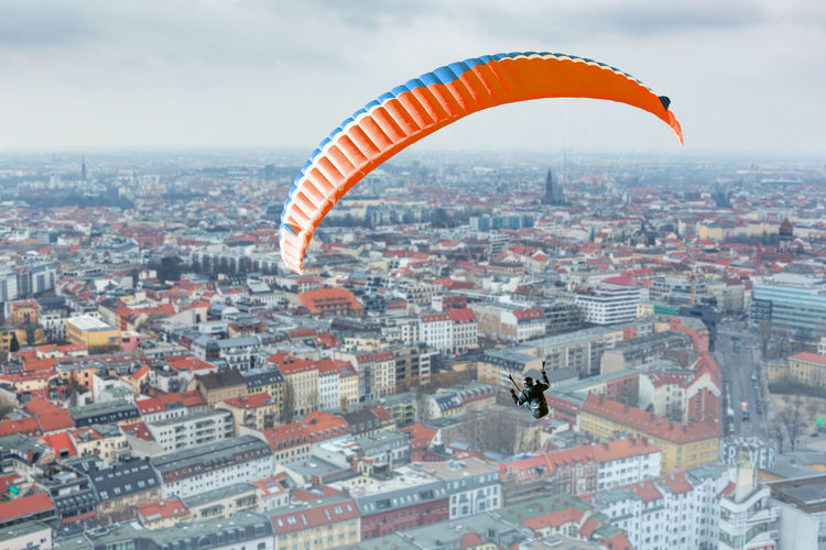 High Angle View Of Woman Paragliding Over Cityscape