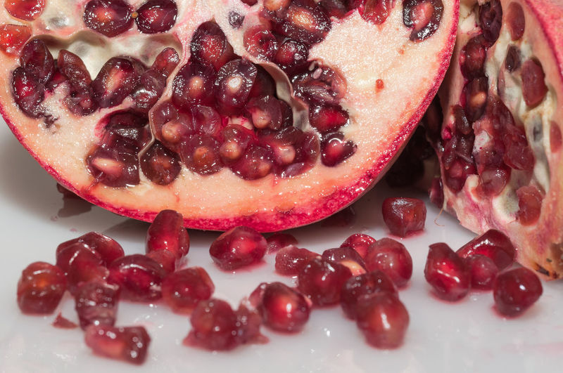 Pomegranate on a white background Cut Red SLICE Seed Antioxidant Close-up Desssert Food Freshness Fruit Glossy Pomegranate Pomegranate Seed Ready-to-eat Ripe Sweet Food Wet White Background