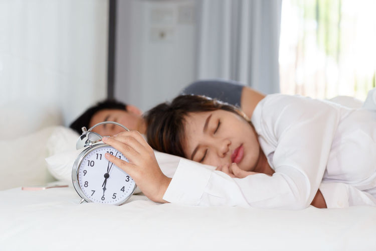 Couple sleeping with alarm clock on bed at home