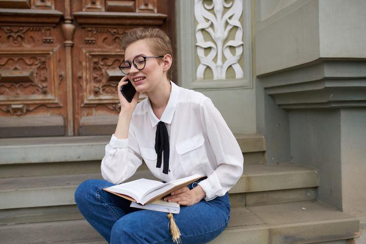 Full length of teenage girl sitting on book