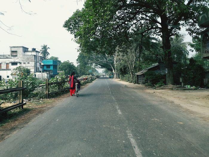 Rear view of man walking on road along plants