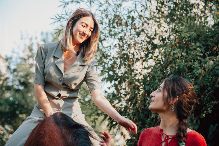 Smiling woman sitting on horse against tree