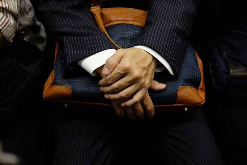 Midsection of businesswoman holding bag