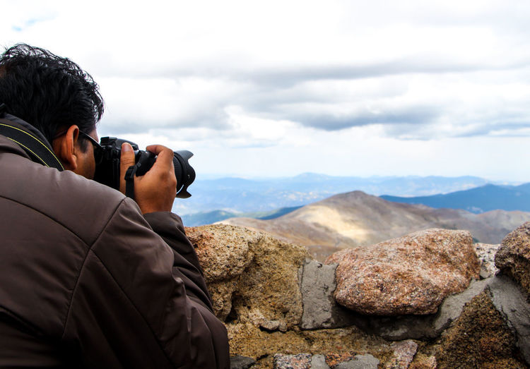 Rear view of photographer photographing mountains against sky