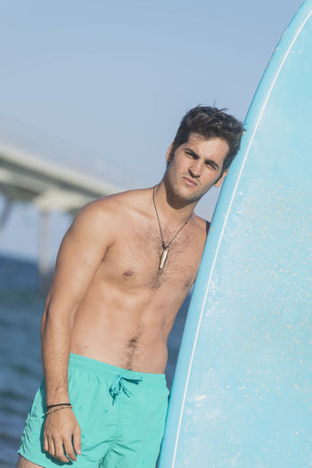 Portrait of shirtless man standing with surfboard at beach