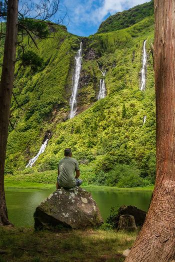 Rear view of mid adult man looking at waterfall while sitting on rock in forest