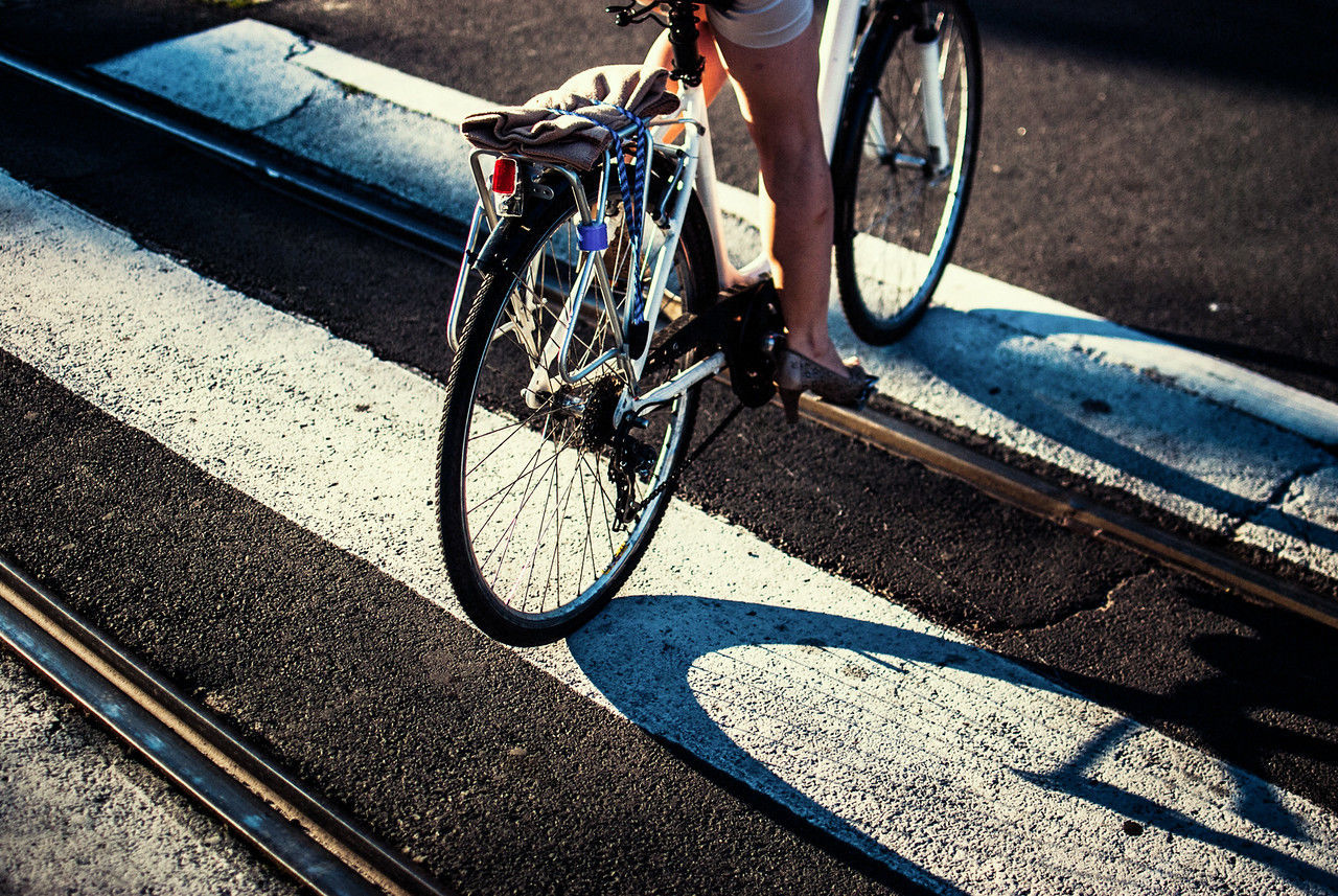 Low section of woman riding bicycle while crossing city street