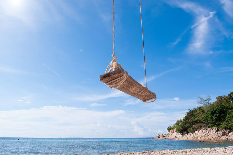 Swing hanging at beach against blue sky