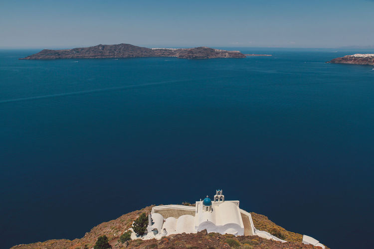 High angle view of church against blue sea on sunny day