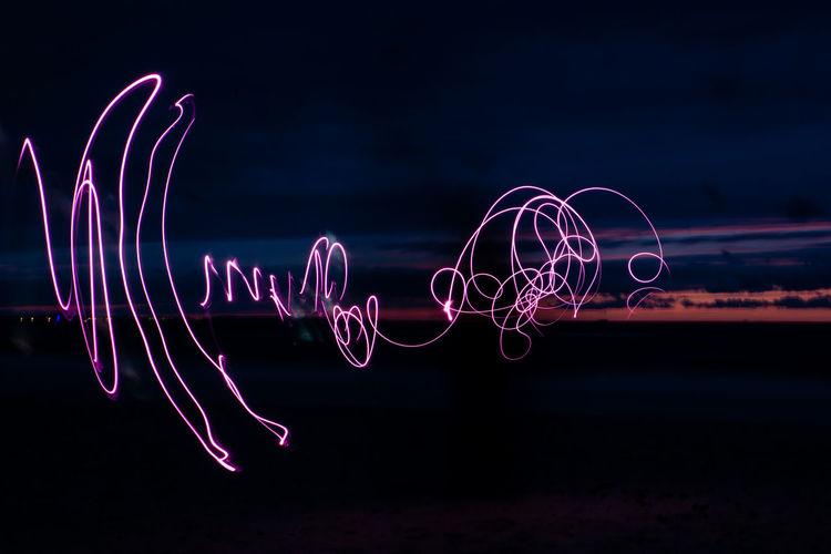 Illuminated light painting against sky at night