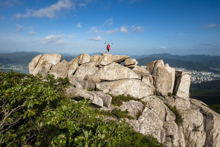 Man On Rock Against Mountain And Sky