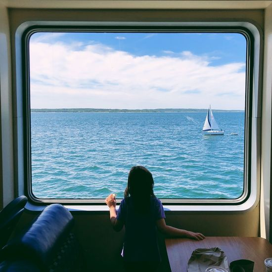 Rear view of woman looking at sea through window