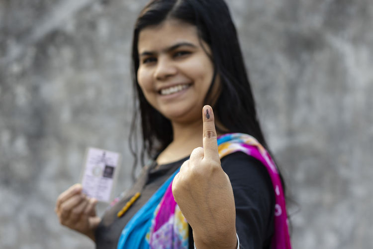 Selective focus on ink-marked finger of an indian woman with smiling face and voter card