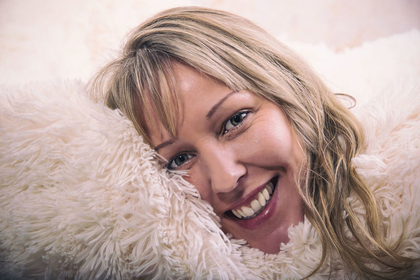 Blonde woman is happy in bright cosy blankie 40 Years Old Happy Laughing Positive Soft Vintage Style Authentic Beautiful Woman Blanket Blond Hair Complacency Cozy Cuddly Face Feeling Good Friendly Joy Looking At Camera Lust Middle Aged Portrait Real Laughing Shining Eyes Smiling Smooch