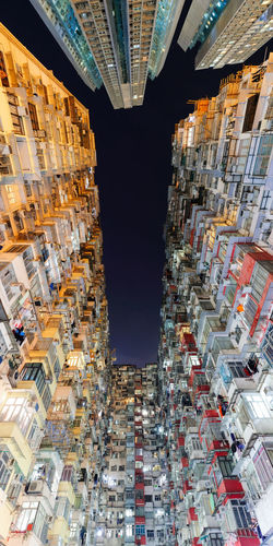 Directly Below Shot Of Illuminated Buildings Against Sky At Night