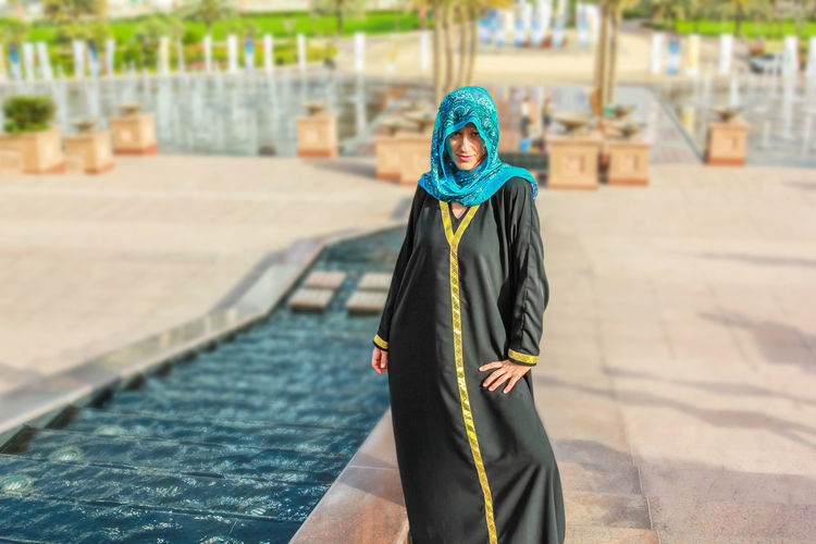 Woman with typical Arab clothes. Luxury vacations and tourism concept. Defocused background at Abu Dhabi, the capital of United Arab Emirates. Holidays, lifestyle and expensive concept. Abu Dhabi UAE United Arab Emirates Woman Abu Dhabi UAE Arab Arabic Beautiful Woman Day Emirates Focus On Foreground Front View Full Length Leisure Activity Lifestyles Looking At Camera One Person Outdoors Palace Portrait Real People Standing Traditional Clothing Woman Portrait Young Adult Young Women