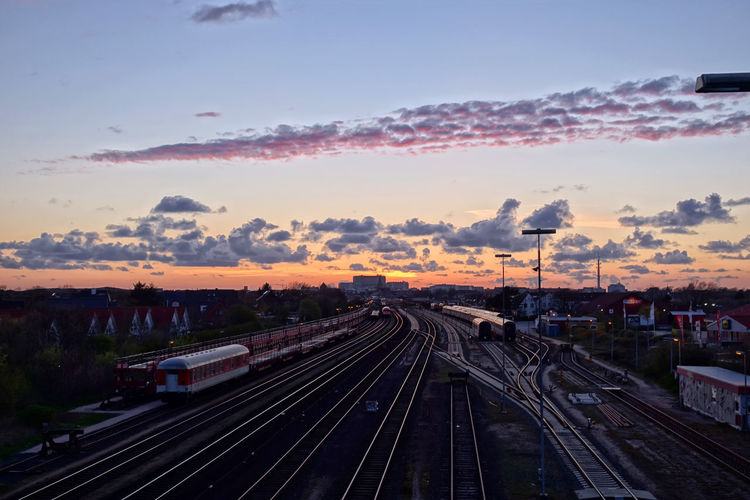 Architecture Sunset Nature Sky Day Outdoors Transportation Railway Track Public Transportation Sylt Railroad Track Westerland No People Rail Transportation Cloud - Sky Building Exterior Built Structure Train - Vehicle It's About The Journey Humanity Meets Technology My Best Photo Track Train Mode Of Transportation High Angle View City Travel