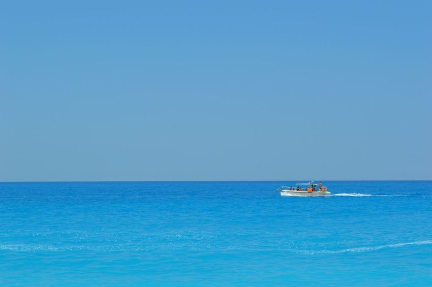 Milos beach in Lefkada Beauty In Nature Blue Boat Calm Clear Sky Day Showcase July Idyllic Mode Of Transport Nature Nautical Vessel No People Non-urban Scene Ocean Outdoors Remote Rippled Sailing Scenics Sea Seascape Sky Tranquil Scene Tranquility Water