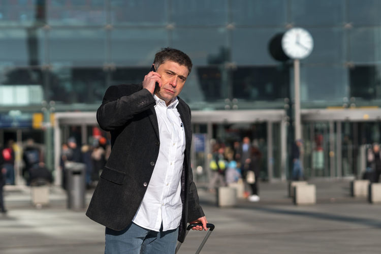 Businessman talking on phone while standing on city street