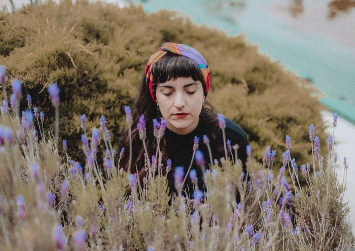 Woman with eyes closed by purple flowering plant