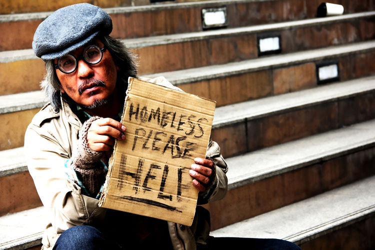 homeless man Helping Helping Homeless People Homeless People Poor  Adult Building Exterior Bum Close-up Day Help Me Homeless Homeless Family Homeless Man Lifestyles No Money One Person Outdoors People People Street Poverty Real People Sitting Warm Clothing Wood - Material Young Adult