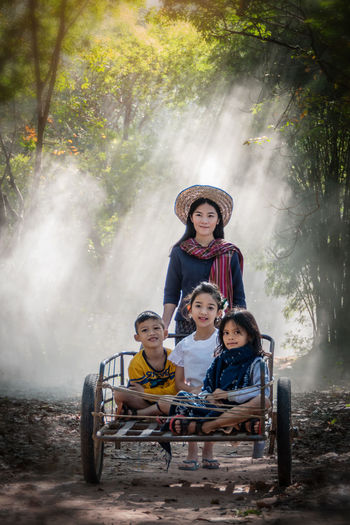 Portrait of smiling mother with children sitting in cart in forest