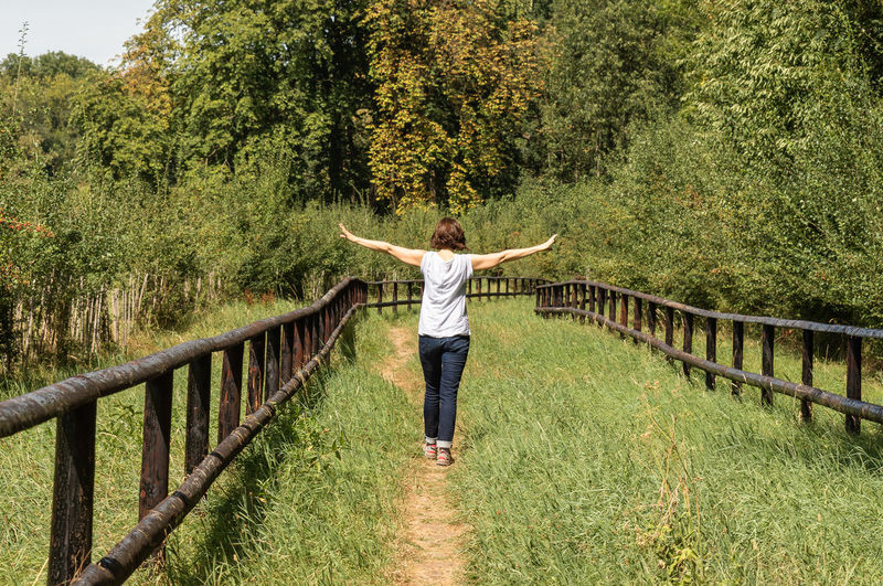 Woman Arms Outstretched Arms Raised Carefree Casual Clothing Day Freedom Full Length Grass Green Color Growth Human Arm Human Limb Land Leisure Activity Limb Nature One Person Outdoors Plant Positive Emotion Real People Tree Young Adult