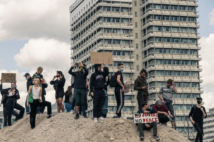 People standing by buildings in city against sky