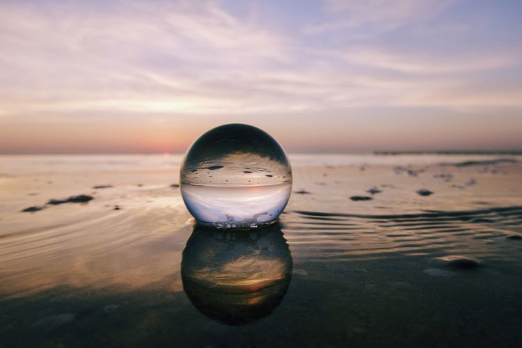 Close-up of crystal ball on beach against sky during sunrise