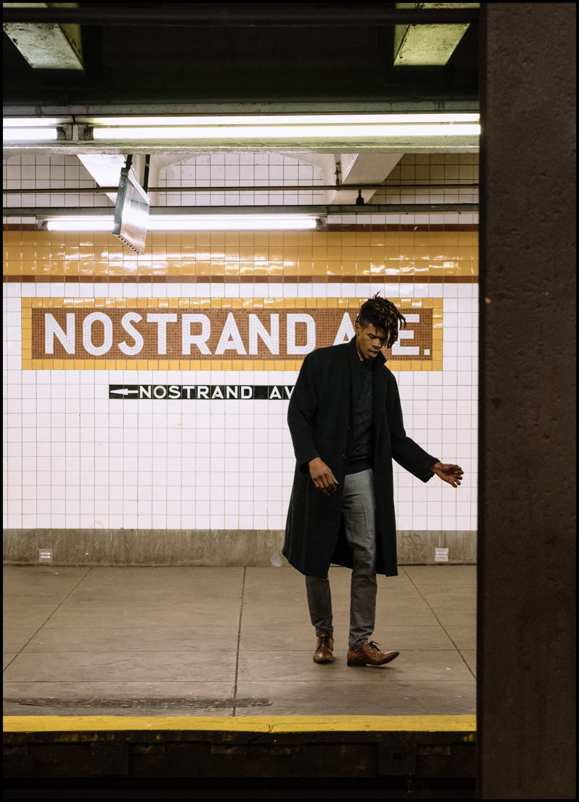 full length, real people, one person, text, young men, standing, casual clothing, communication, men, leisure activity, lifestyles, architecture, young adult, built structure, indoors, transportation, public transportation, subway station, waiting