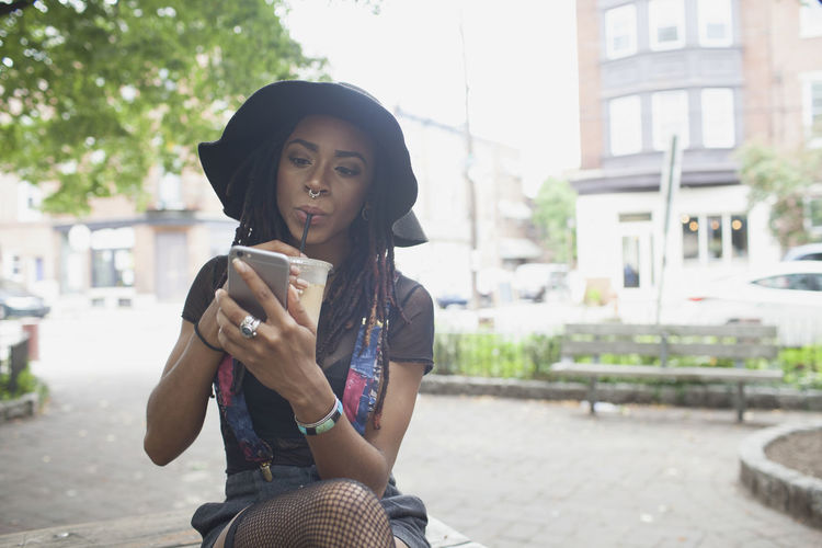 Portrait of young woman using phone in city