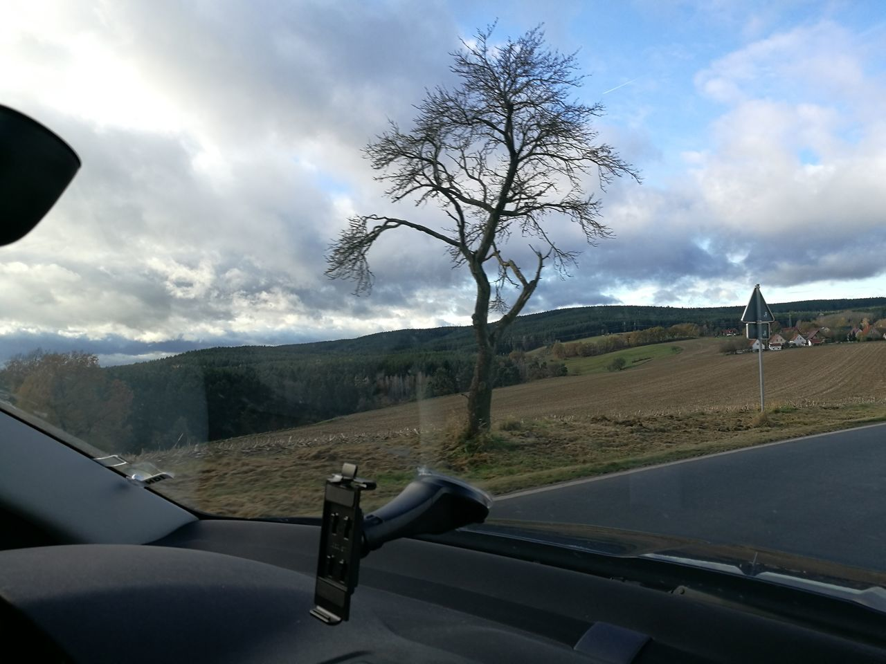 transportation, land vehicle, car, mode of transport, vehicle interior, mountain, car interior, windshield, cloud - sky, sky, day, landscape, road, bare tree, tree, travel, road trip, no people, mountain range, nature, outdoors, beauty in nature