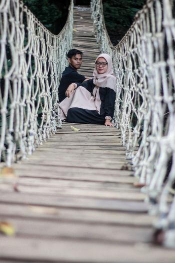 People sitting on footbridge