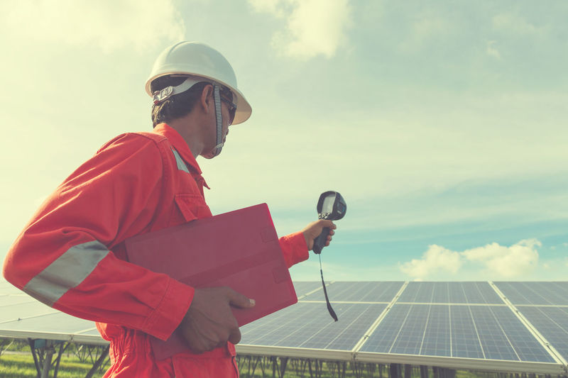 Low angle view of male technician holding equipment against solar panels
