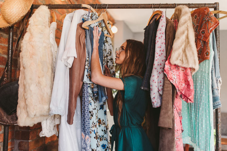 Clothing One Person Choice Indoors  Fashion Women Store Variation Dress Coathanger Retail  Shopping Clothing Store Standing Adult Hanging Hairstyle Long Hair Rack Decisions Consumerism Closet Boutique Contemplation Getting Dressed