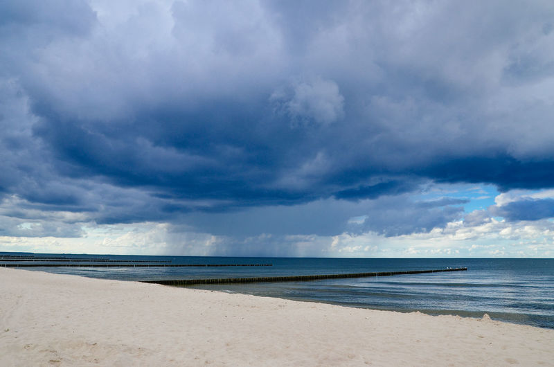 View of calm beach against cloudy sky