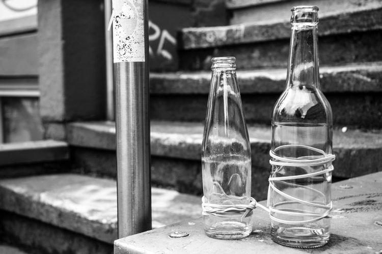 Empty Bottles Tied With Threads On Table By Steps