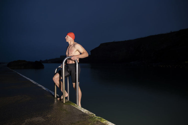 Man standing in lake against sky