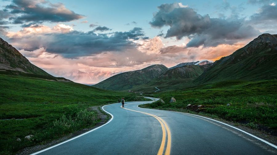 Road leading towards mountains against sky