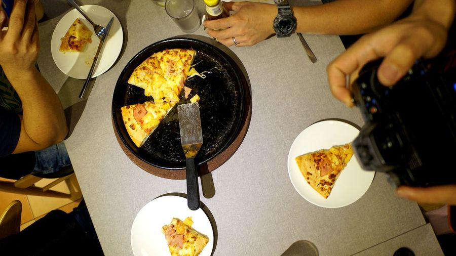Cropped Image Of Friends Having Pizza In Restaurant