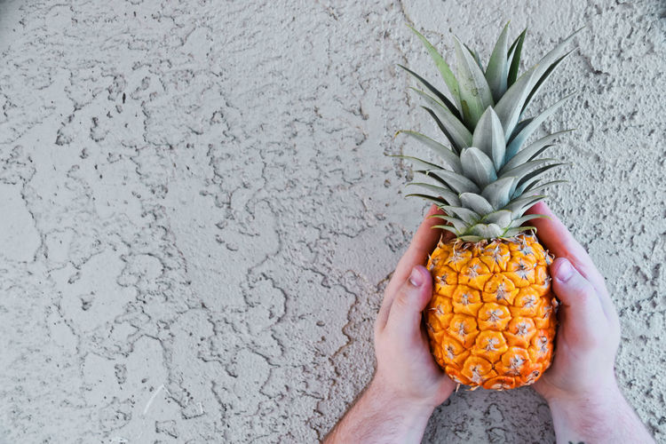 Cropped hands of man holding pineapple against wall
