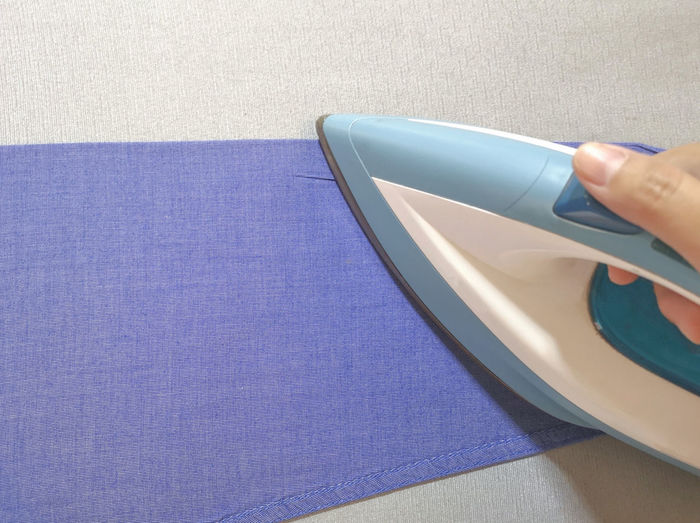 the hand is ironing blue shirt. Iron Hand Indoors  Table Close-up Ironing Laundry Housework Domestic Household Clothes Electric Housekeeping Shirt Appliance Cloth Dry Housewife Equipment Clean Heat Blue Woman Smooth Holding
