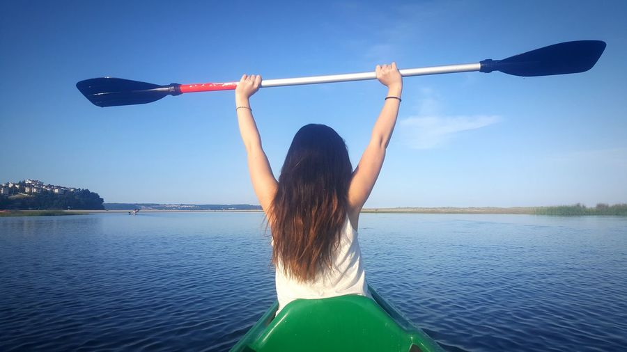 Rear view of woman canoeing on river