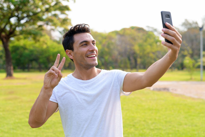 Smiling young man using smart phone outdoors