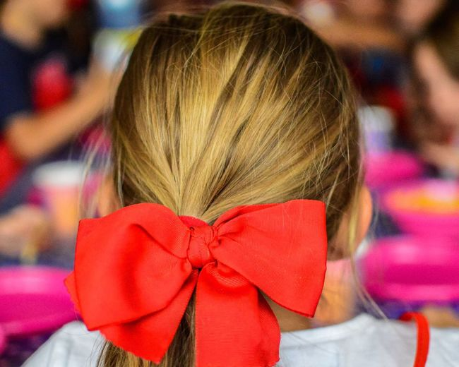 Rear view of girl with red tied bow