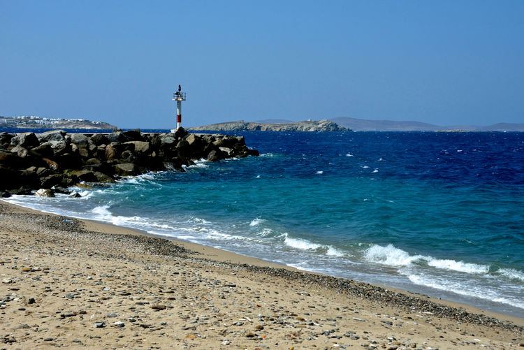 panoramic seascape in Mykonos seen from a pebble and sandy bech with pier with light equipment Sea Beach Water Land Beauty In Nature Sky Scenics - Nature Nature Tower Rock Guidance Built Structure Blue Architecture Wave Direction Lighthouse Horizon Horizon Over Water No People Outdoors Light Equipment Navigation Light Pier Port Waves Nature Travel Destinations Panorama Seascape