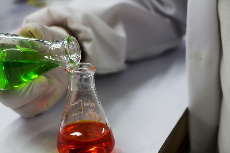 Cropped Hand Of Person Pouring Chemical In Beaker On Table