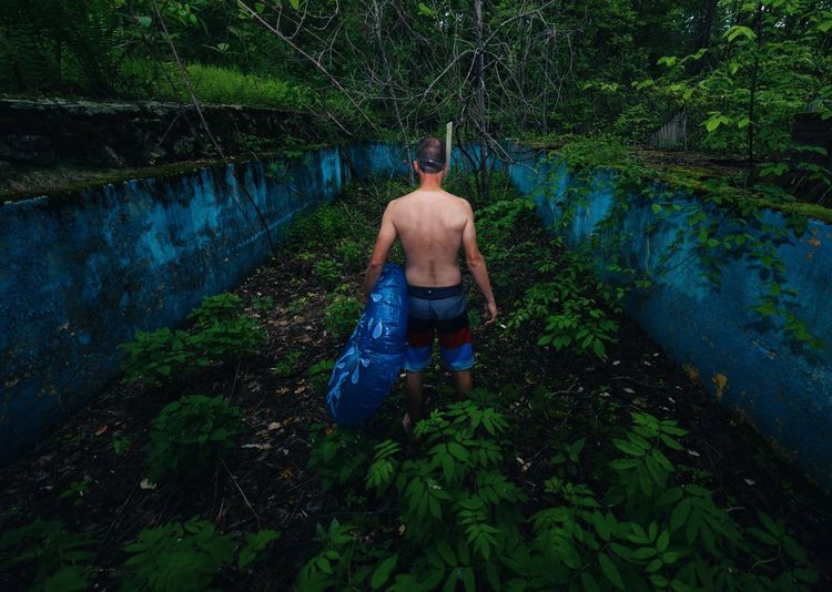 Rear view of man holding inflatable ring while standing amidst plants at forest